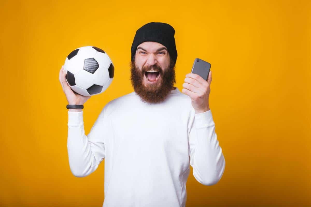 Un homme content avec un ballon de football et un smartphone